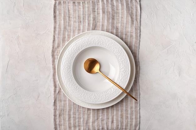 Piatto bianco vuoto e cucchiaio d'oro sugli utensili da cucina del tovagliolo messi sul piano del tavolo grigio chiaro