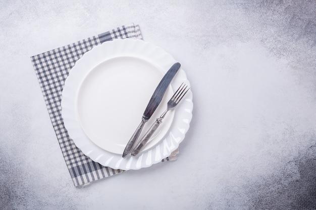 Piatto bianco vuoto, tovagliolo di lino, coltello e forchetta su fondo di pietra
