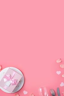 Piatto bianco vuoto con regalo e petali di rosa per il concetto di pasto di datazione di festa speciale di san valentino.