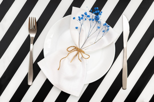 Un piatto bianco vuoto con un tovagliolo e fiori a forma di fiocco e un coltello da forchetta sul tavolo a strisce bianche nere