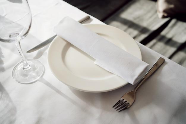 Piatto bianco vuoto con tovagliolo, coltello e forchetta