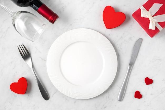 Piatto bianco vuoto con stoviglie per il concetto di pasto datazione vacanza speciale di san valentino.