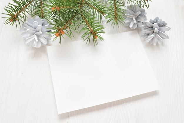Foglio di carta bianco vuoto su uno sfondo bianco di natale di rami di abete