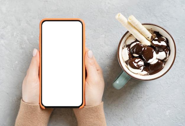 Applicazione dello schermo dello smartphone bianco vuoto e tazza di cioccolata calda. modello per lo spazio della copia.