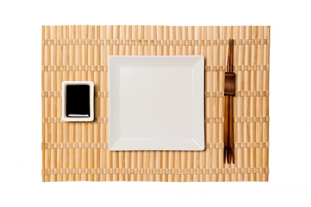 Piatto quadrato bianco vuoto con le bacchette per sushi e salsa di soia sulla stuoia di bambù giallo. vista dall'alto con spazio di copia per il tuo design