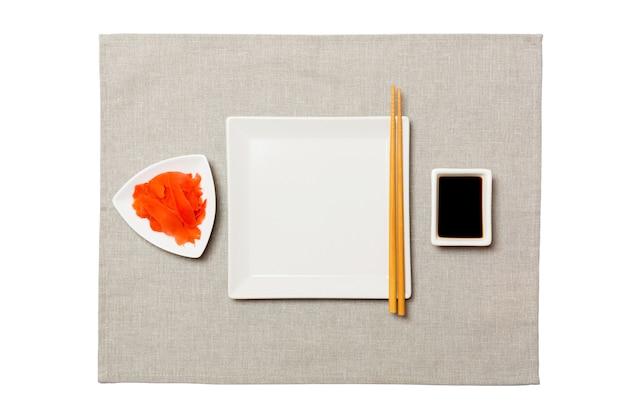 Piatto quadrato bianco vuoto con bacchette per sushi