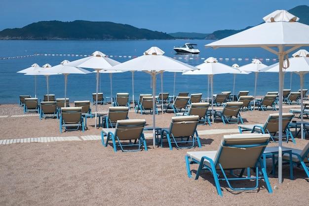 Sedie a sdraio bianche vuote senza persone sotto l'ombrellone sulla spiaggia di ciottoli in riva al mare