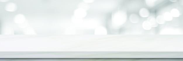 Piano d'appoggio bianco vuoto, bancone, scrivania sopra il negozio di prospettiva di sfocatura con sfondo chiaro bokeh