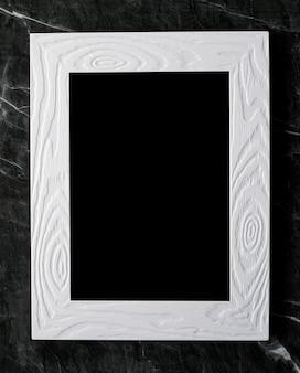 Struttura di legno d'annata bianca vuota sul fondo di marmo nero del pavimento