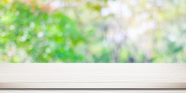Svuoti la tavola di legno bianca sopra l'albero vago con il fondo del bokeh, per il montaggio dell'esposizione del prodotto