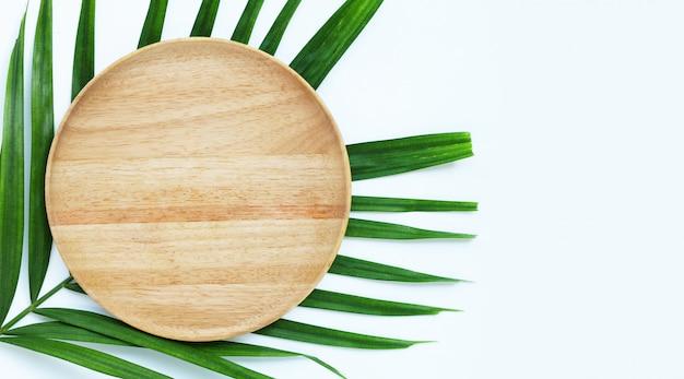 Piatto di legno bianco vuoto su foglie di palma tropicale su sfondo bianco.