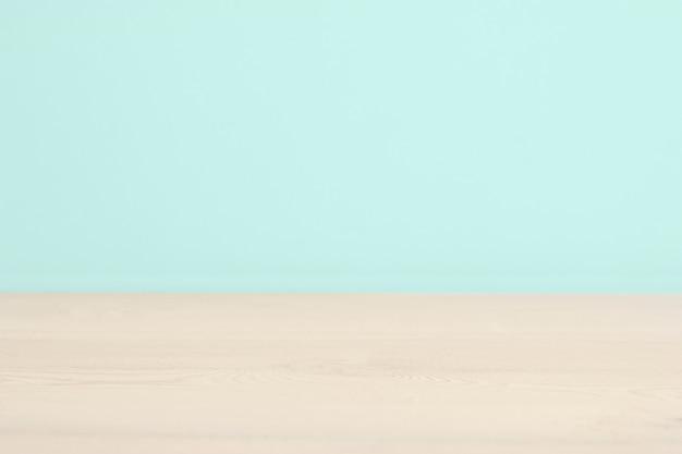 Svuotare un tavolo in legno bianco e uno sfondo azzurro. copia spazio