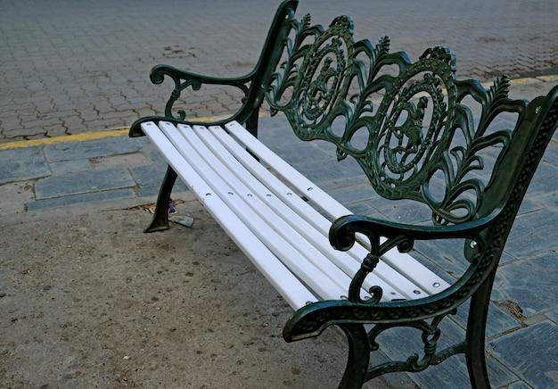 Vuoto in legno bianco con panca vintage in ferro battuto verde scuro sulla piazza