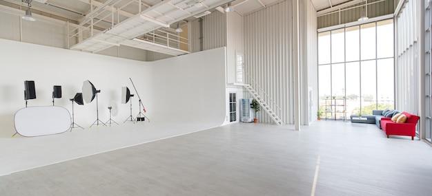 Stanza del laboratorio di studio fotografico di design industriale per interni, ampia e alta, piena di spazio e attrezzatura fotografica professionale posizionata su parete e pavimento bianchi con lampadine e condizionatore d'aria.
