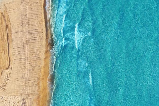 Spiaggia selvaggia vuota con sabbia dorata e acqua blu