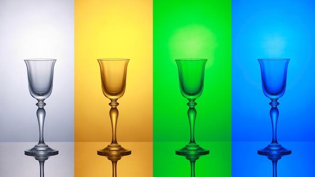 Bicchiere di vino vuoto su un baground a strisce blu verde giallo bianco