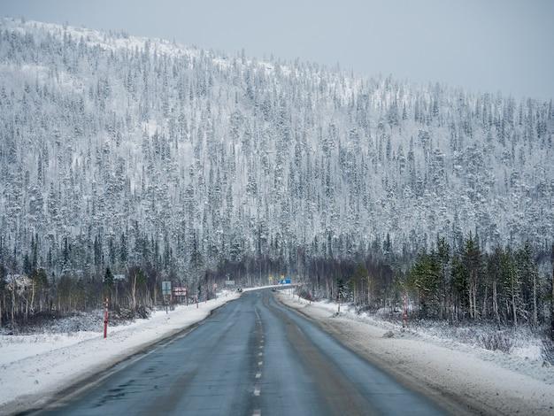 Strada artica di inverno vuoto attraverso le colline.