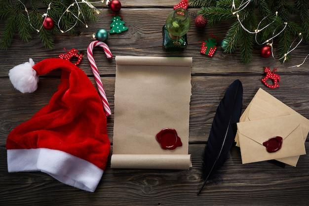 Lista dei desideri vuota per babbo natale sulla tavola di legno con decorazioni natalizie.