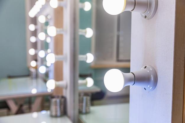 Posto vuoto per il trucco della donna con specchio e lampadine. truccatore sul posto di lavoro nella moderna sala trucco. interni da barbiere. spogliatoio con specchio per il trucco e tavolo. interior design moderno in stile classico.