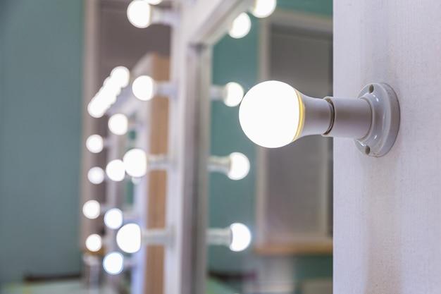 Posto vuoto per il trucco della donna con specchio e lampadine. truccatore sul posto di lavoro nella moderna sala trucco