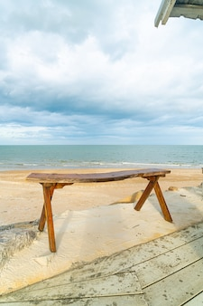 Panca di legno vuota sulla spiaggia con sfondo di spiaggia di mare