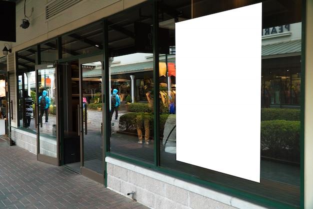 Esposizione vuota del manifesto della struttura di legno sulla finestra di vetro alla stanza frontale di negozio del negozio