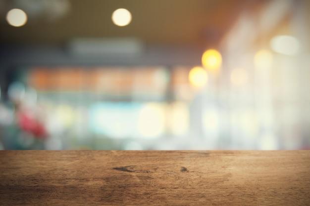 Tavola di legno vuota sul fondo della caffetteria della sfuocatura