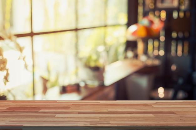 Tavolo di legno vuoto e sfocato visualizzazione di sfondo presso il negozio di caffè con spazio per il prodotto.