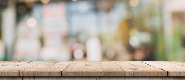 Tavolo in legno vuoto e tavolo luminoso sfocato in caffetteria e caffetteria con sfondo bokeh di fondo. modello di visualizzazione del prodotto.
