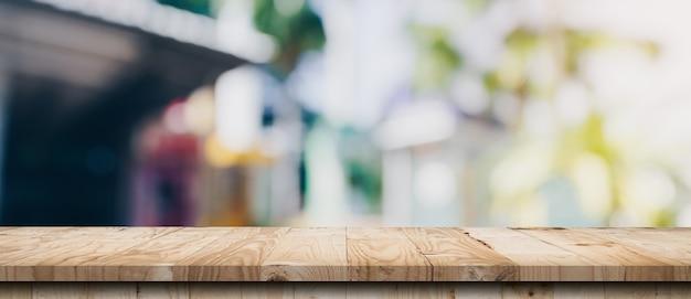 Tavolo in legno vuoto e tavolo luminoso sfocato in caffetteria e bar con sfondo bokeh. modello di visualizzazione del prodotto.