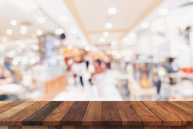 Tavola di legno vuota e tavola leggera vaga nel centro commerciale con il fondo del bokeh. modello di visualizzazione del prodotto.
