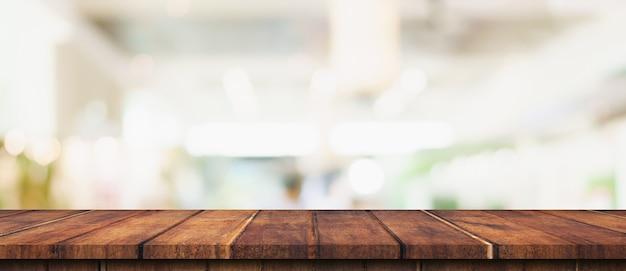 Tavolo in legno vuoto e tavolo luminoso sfocato nel centro commerciale con sfondo bokeh di fondo. modello di visualizzazione del prodotto.