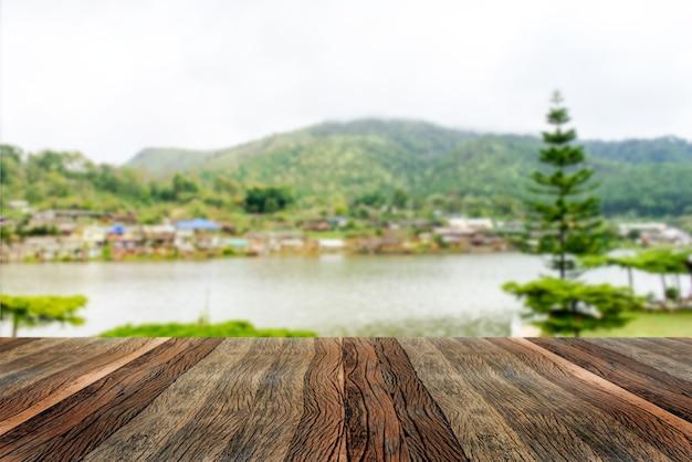 Tavolo in legno vuoto e piscina sfocata e paesaggio di montagna al mattino.