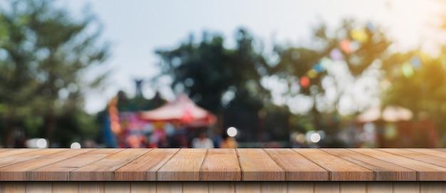 Tavolo in legno vuoto e bokeh sfocato e sfocatura dello sfondo di alberi da giardino alla luce del sole, montaggio del display per il prodotto.