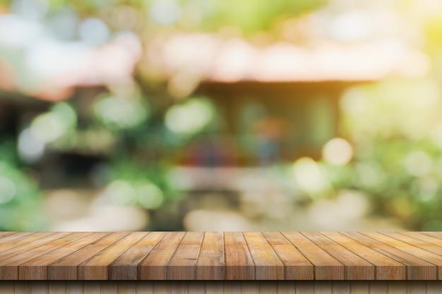 Tavolo in legno vuoto e bokeh sfocato e sfondo sfocato di alberi da giardino con luce solare. modello di visualizzazione del prodotto.