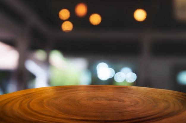Tavolo di legno vuota davanti alla caffetteria offuscata caffetteria o sfondo sul posto di lavoro