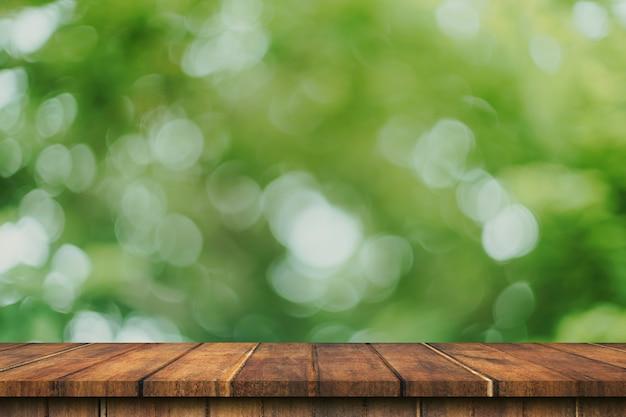 Tavola di legno vuota e sfocatura verde del bokeh con montaggio dell'esposizione dello spazio della copia per prodotto.