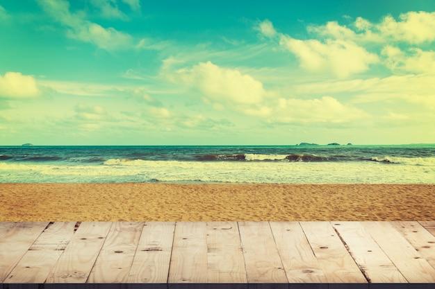 Tavolo in legno vuoto per la visualizzazione del prodotto e montaggio sulla spiaggia con annata tonica.
