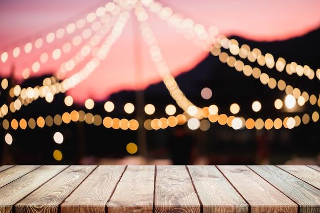 Piano d'appoggio di legno vuoto sul ristorante vago astratto e sulle luci del partito di campeggio