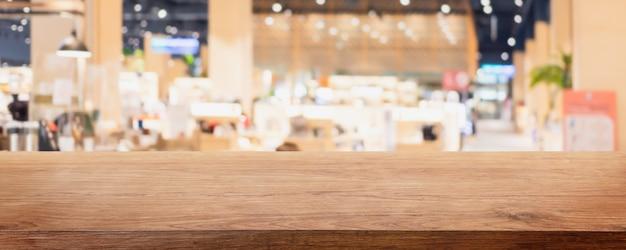 Svuoti il piano d'appoggio di legno e il ristorante e il caffè interni della finestra di vetro della sfocatura
