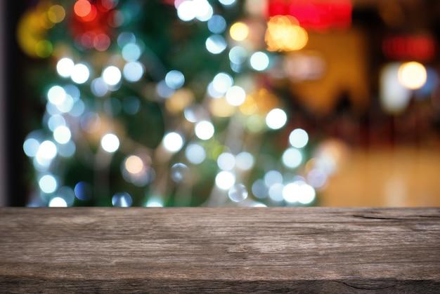 Svuoti il piano d'appoggio di legno e la sfuocatura della celebrazione brillante del nuovo anno di natale della luce notturna delle lampadine di lustro