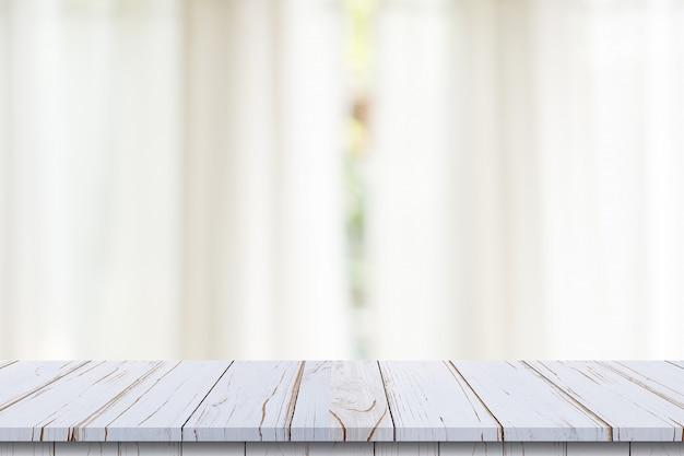 Piano d'appoggio di legno vuoto sul fondo bianco della finestra della sfuocatura. per il montaggio di prodotti o alimenti.