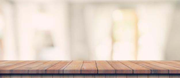 Piano del tavolo in legno vuoto sulla sfocatura dello sfondo della finestra bianca. per il montaggio di prodotti o alimenti.