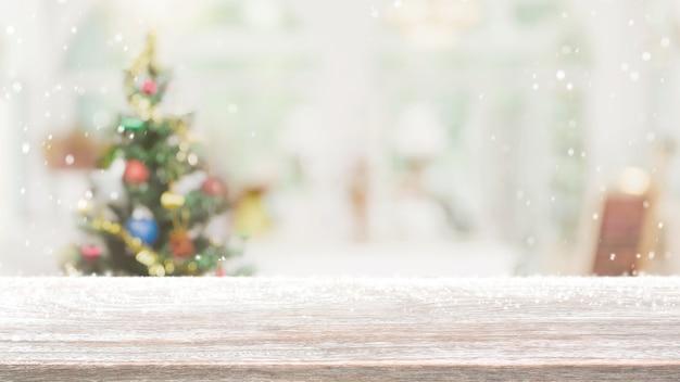 Piano del tavolo in legno vuoto su sfocatura con bokeh albero di natale e decorazione di capodanno su sfondo banner finestra con nevicata - può essere utilizzato per visualizzare o montare i tuoi prodotti.