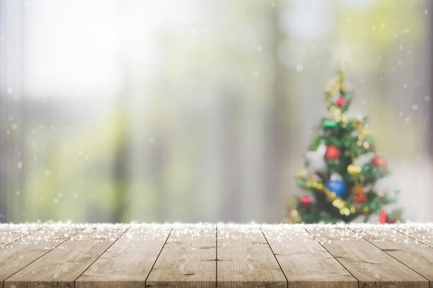 Svuoti il piano d'appoggio di legno sulla sfuocatura con l'albero di natale del bokeh e la decorazione del nuovo anno sulla finestra