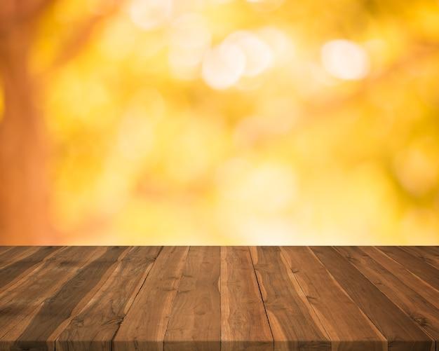 Tavolo in legno vuoto vuoto su sfondo autunnale astratto offuscata, spazio libero per la modifica dei prodotti.