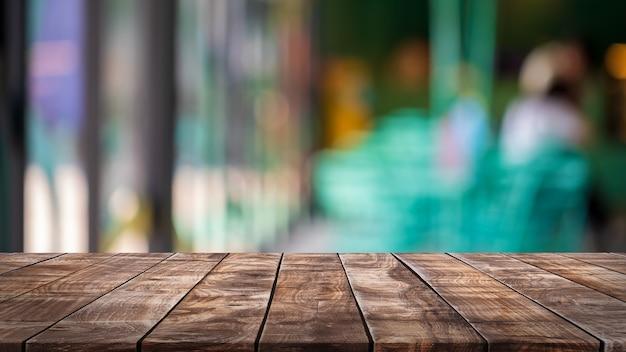 Piano del tavolo in legno vuoto e sfondo sfocato della caffetteria, del bar e del ristorante interno - può essere utilizzato per visualizzare o montare i tuoi prodotti.