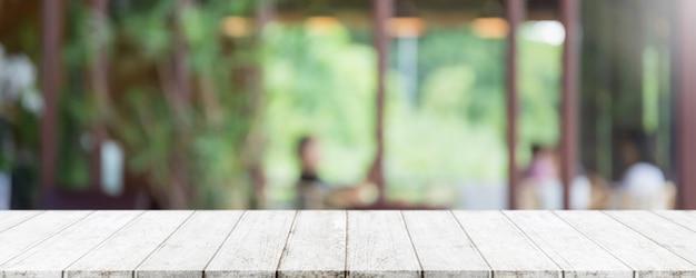 Piano d'appoggio in legno vuoto e interni sfocati di caffetteria, bar e ristorante
