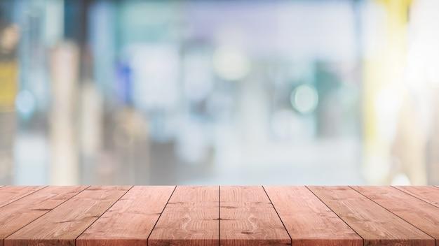Piano del tavolo in legno vuoto e caffetteria sfocata e sfondo interno del ristorante - può essere utilizzato per visualizzare o montare i tuoi prodotti. Foto Premium