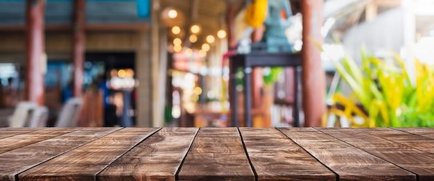 Piano del tavolo in legno vuoto e caffetteria sfocata e sfondo interno del ristorante - può essere utilizzato per visualizzare o montare i tuoi prodotti.